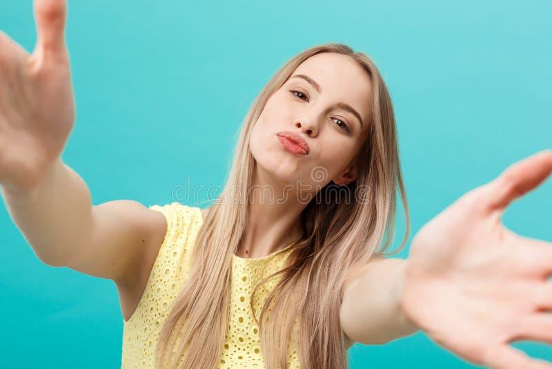 Портрет конца-вверх привлекательной молодой женщины протягивая ее оружия, хочет обнять и расцеловать вас Изолировано на голубой п стоковое фото rf