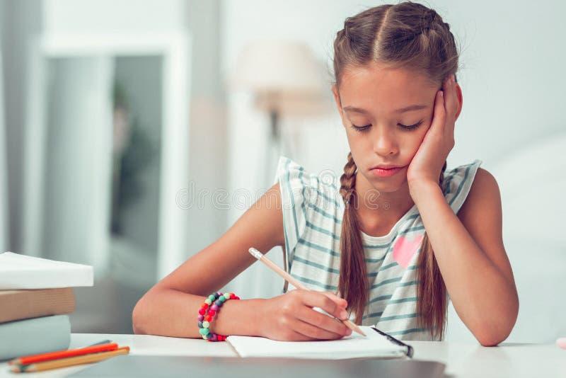 Портрет конца-вверх пробуренной милой Афро-американской девушки делая пишущ домашнюю работу стоковое фото rf