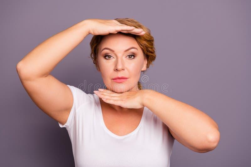 Портрет конца-вверх славного привлекательного содержания хорошо выхолил волнист-с волосами даму нося случайный белый показывать ф стоковое фото rf