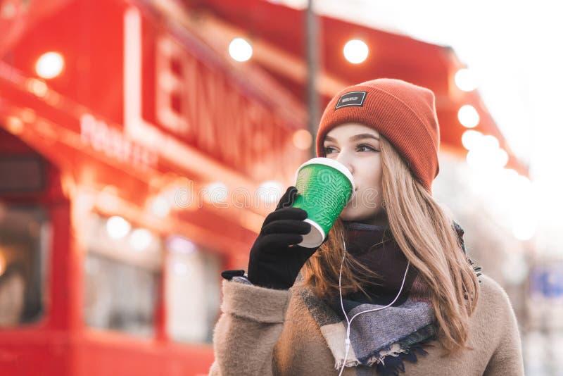 Портрет конца-вверх сладкой дамы в теплых одеждах выпивает кофе в яркой красной предпосылке города Красивая девушка в выпивать кр стоковые изображения