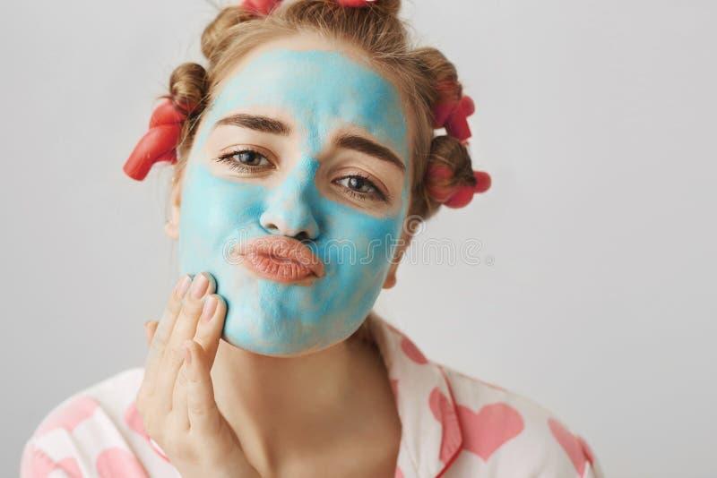 Портрет конца-вверх смешной белой женщины с волос-curlers, нося nightwear и складывая губами пока прикладывающ лицевой щиток герм стоковое изображение rf