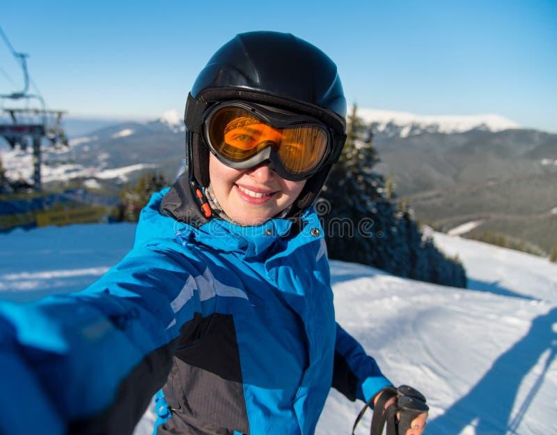Портрет конца-вверх счастливого лыжника женщины усмехаясь, принимая selfie пока отдыхающ на наклоне после кататься на лыжах стоковые фотографии rf