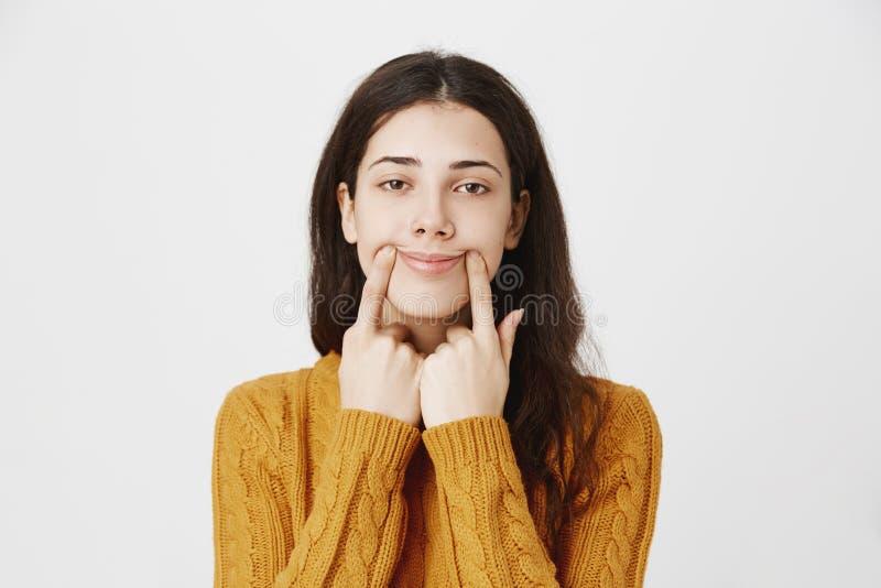 Портрет конца-вверх утомленной и хмурой кавказской прокалыванной девушки протягивая рот с пальцами, делая поддельную улыбку пока стоковые фотографии rf