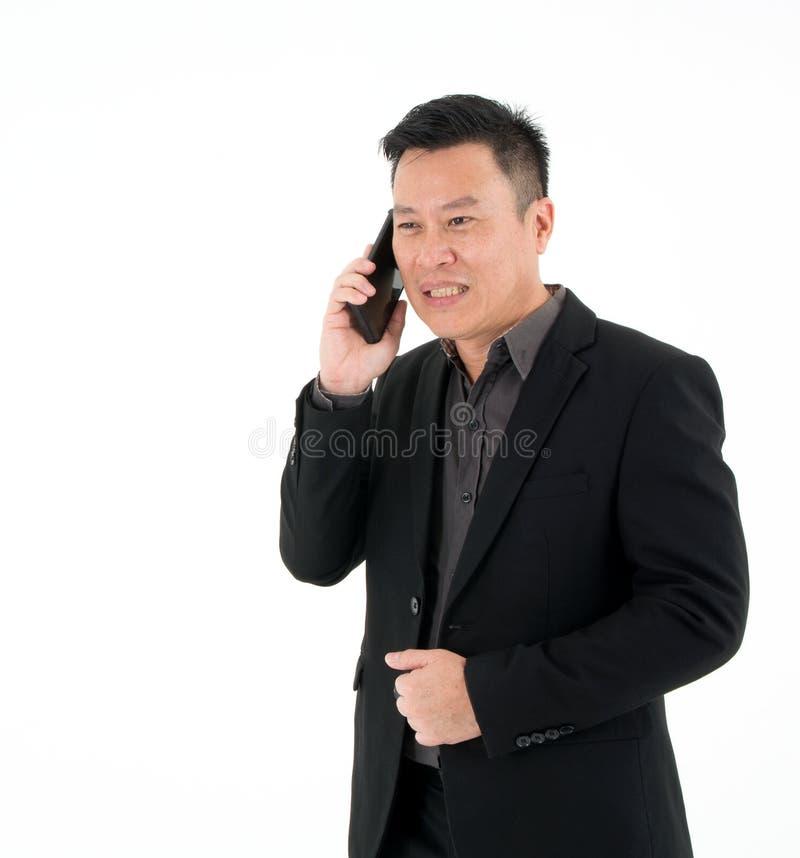 Портрет концентратов бизнесмена серьезно говоря на мобильном телефоне изолированном на белой предпосылке стоковые изображения rf