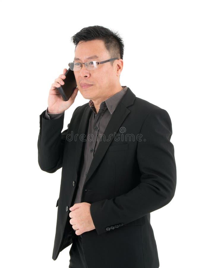 Портрет концентратов бизнесмена серьезно говоря на мобильном телефоне изолированном на белой предпосылке стоковая фотография rf