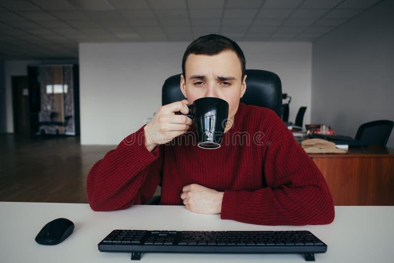 Портрет кофе утомленного молодого работника офиса выпивая на работе Ситуация в офисе стоковое изображение rf