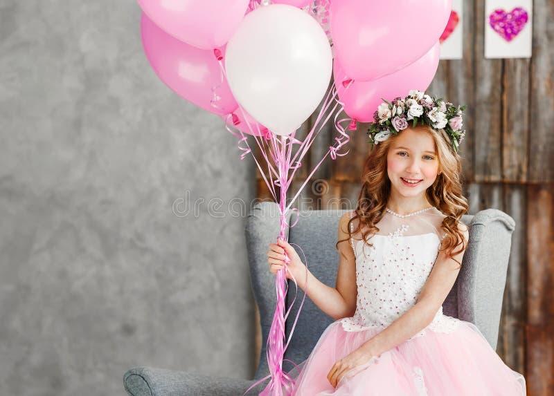 Портрет красивая маленькая девочка в венке свежих цветков и элегантного розового платья празднует ее день рождения в белой студии стоковые фото