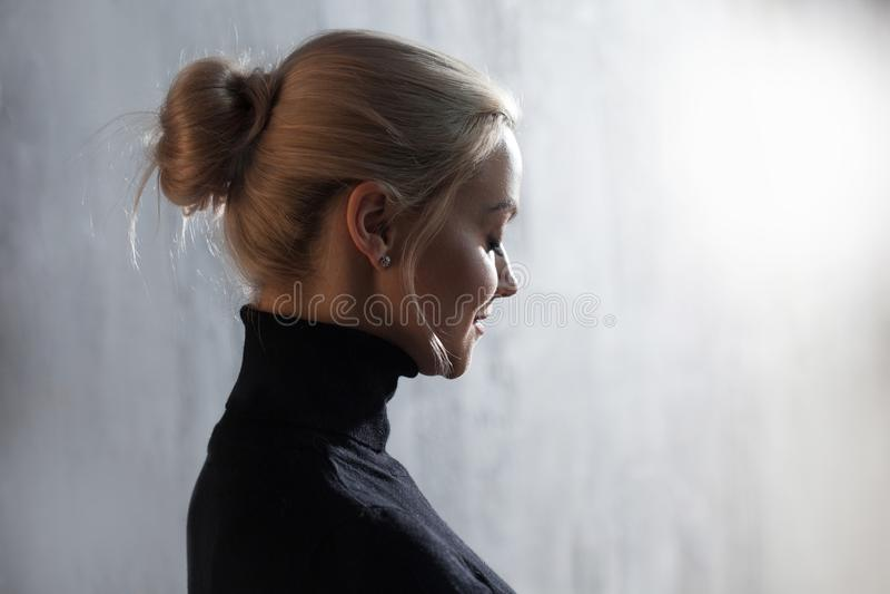 Портрет красивейшей белокурой женщины Затишье и самоуверенность Красивая взрослая девушка в черном turtleneck, серой предпосылке стоковое изображение