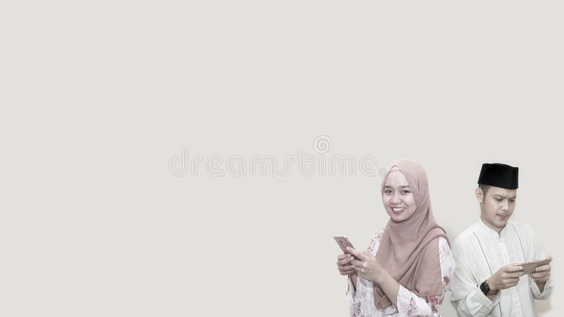 Портрет красивого азиатского мусульманского человека и женщин с головной крышкой и шарфом используя смартфон с космосом экземпляр стоковое изображение rf