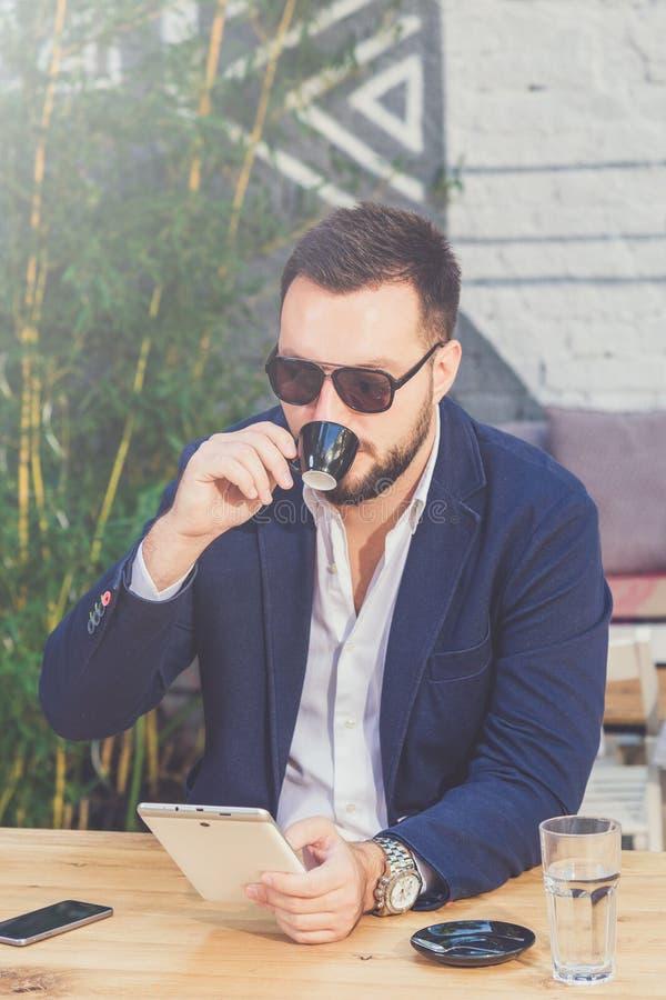 Портрет красивого бизнесмена держа цифровой планшет и выпивая кофе стоковое фото