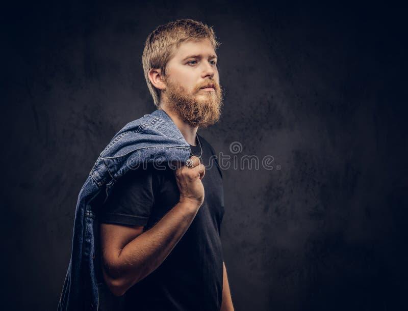 Портрет красивого битника парень одел в черной футболке держит куртку джинсов и смотреть прочь на темной предпосылке стоковые фото