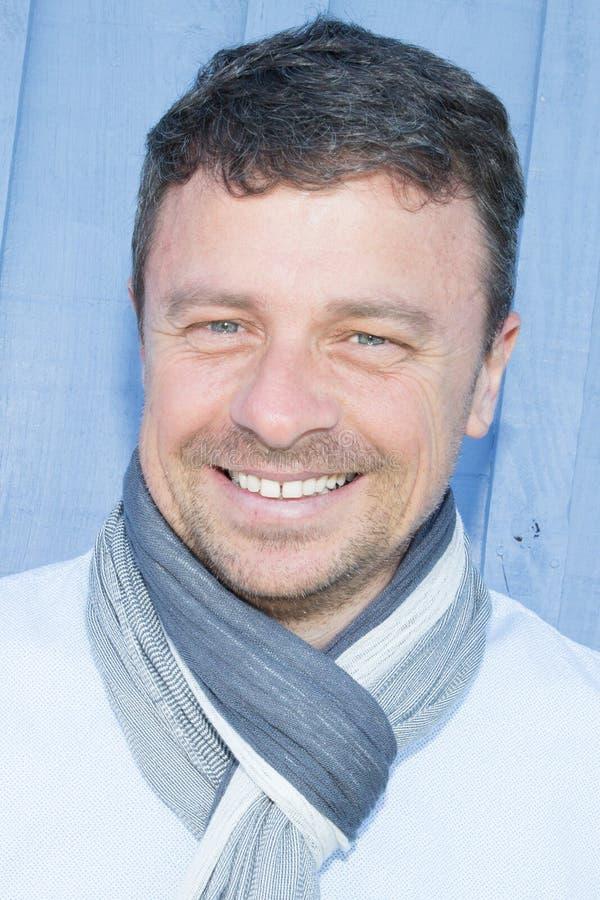 Портрет красивого более старого человека в голубой рубашке и scraf с большой улыбкой на его стороне стоковые фотографии rf