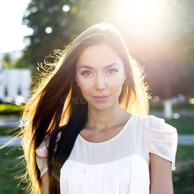 Портрет красивого брюнет в парке в ярком солнечном свете Городская жизнь стиля моды, эмоционально смотрит напольно стоковые изображения