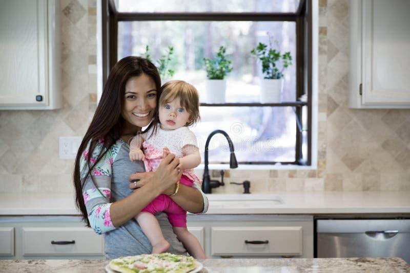 Портрет красивого брюнет усмехаясь с ребёнком в ее руках стоковая фотография