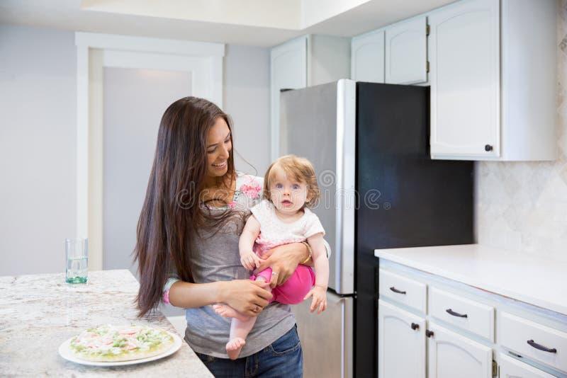 Портрет красивого брюнет усмехаясь с ребёнком в ее руках стоковые фото