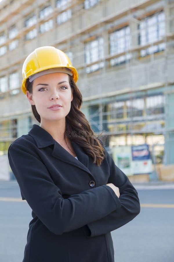 Портрет красивого женского подрядчика нося трудную шляпу на конструкции s стоковые фото