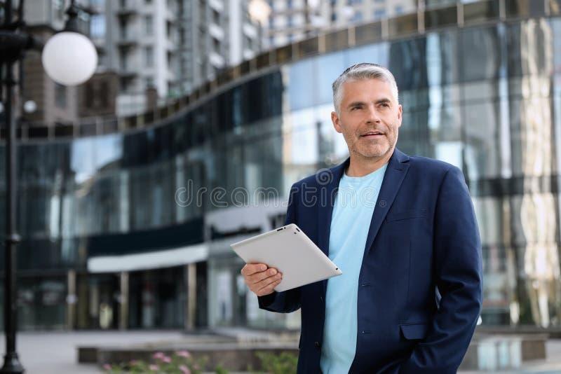 Портрет красивого зрелого человека с планшетом в центре города стоковые изображения