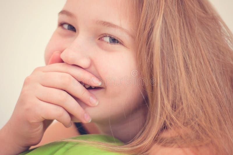 Портрет красивого и счастливого молодого усмехаясь ребенк который ` s покрывая ее рот и зубы с ее рукой стоковые изображения