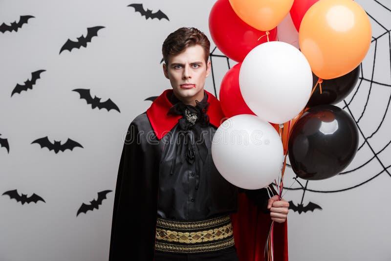 Портрет красивого кавказца в костюме хеллоуина вампира с красочным воздушным шаром стоковое фото rf