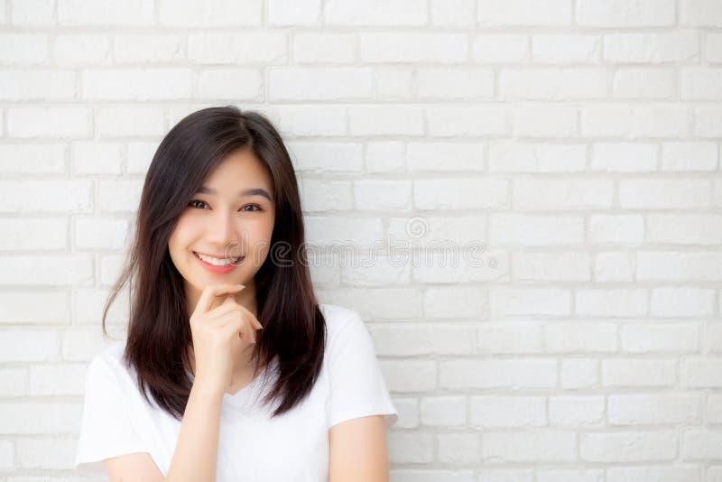 Портрет красивого молодого азиатского счастья женщины стоя на серой предпосылке кирпича стены grunge текстуры цемента стоковое изображение