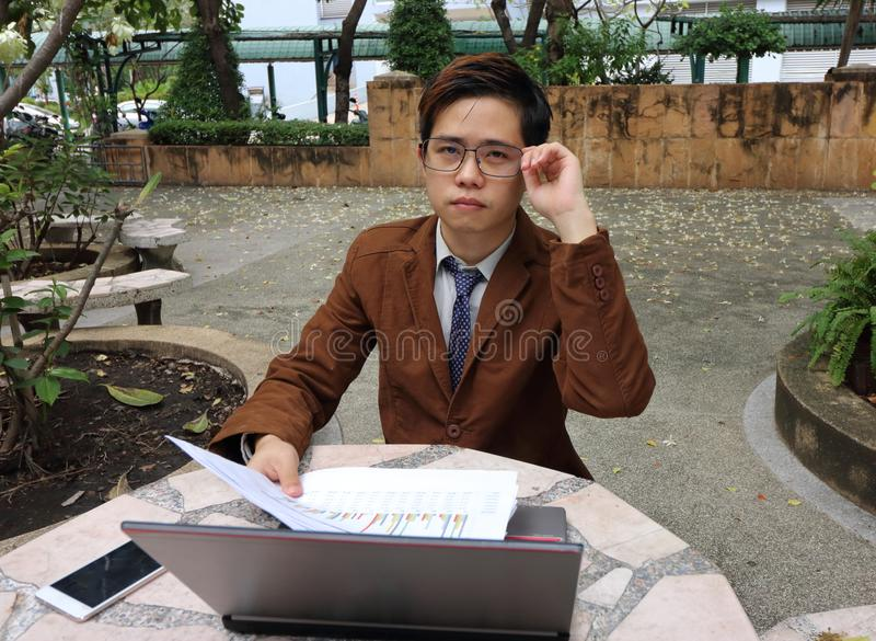 Портрет красивого молодого бизнесмена касается его стеклам и камере взгляда стоковое фото rf