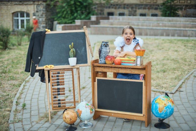 Портрет красивого молодого перво-грейдера сидя на столе на парке осени предпосылки Прощальный колокол день знания стоковая фотография rf