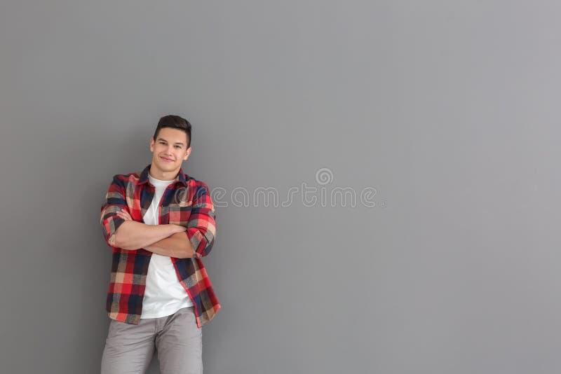 Портрет красивого молодого человека в случайных одеждах на серой предпосылке стоковое фото