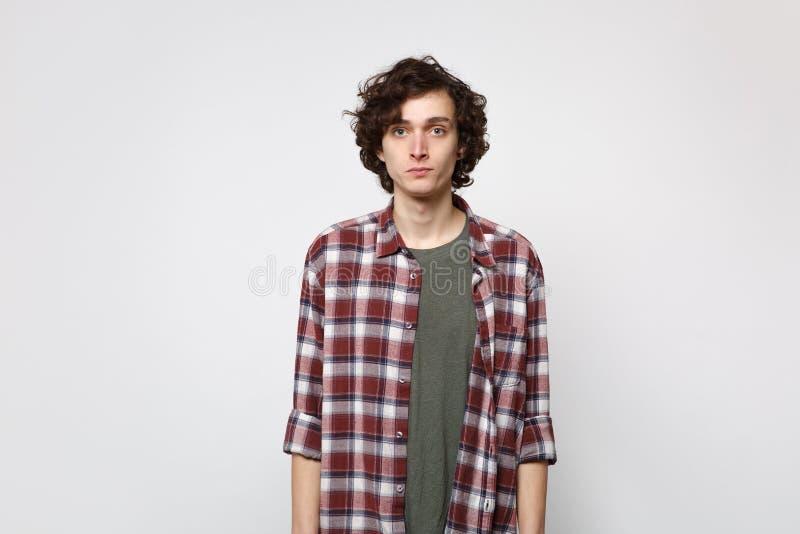 Портрет красивого молодого человека в случайных одеждах стоя, смотря камеру изолированную на белой предпосылке стены в студии стоковое изображение rf
