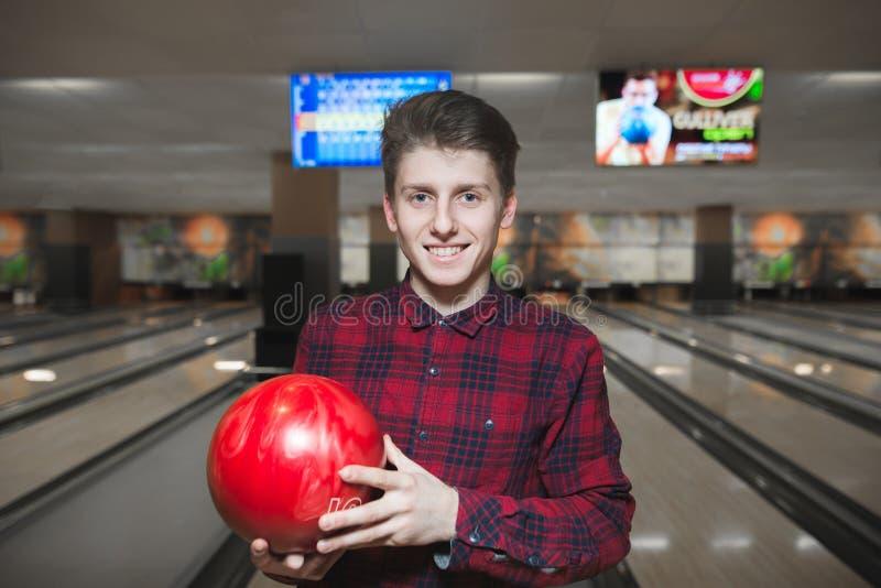 Портрет красивого молодого человека играя боулинг и усмехаться Положительный молодой человек с красным шариком боулинга в его рук стоковая фотография rf
