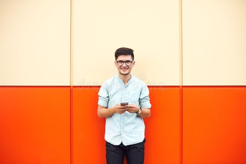Портрет красивого молодого человека используя его чернь в улице над оранжевой стеной стоковые изображения