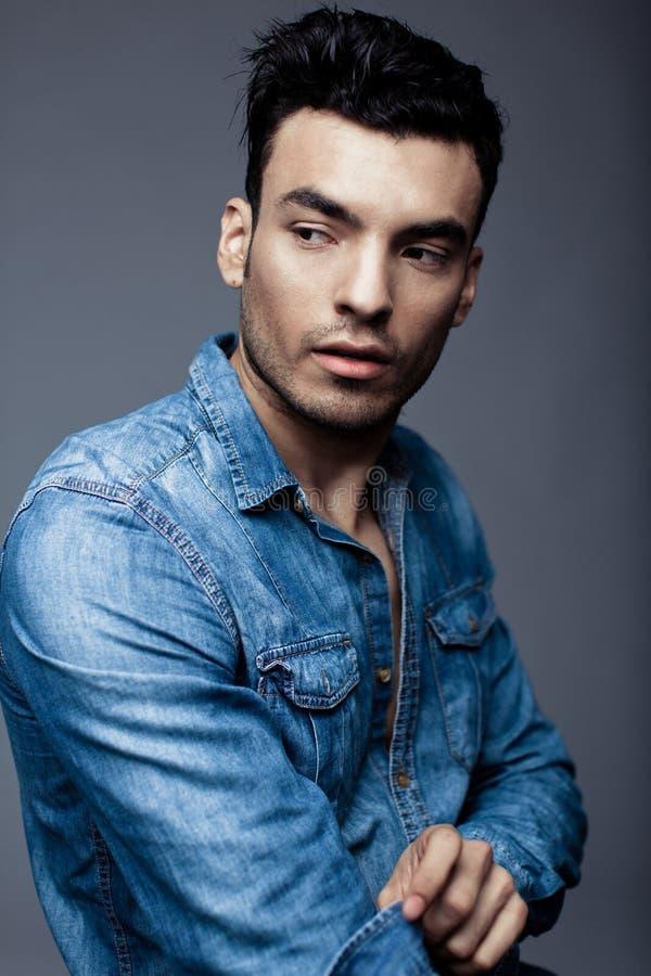 Портрет красивого молодого человека в вскользь джинсовой ткани одевает стоковое изображение
