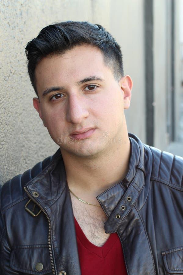 Портрет красивого молодого человека с нейтральным выражением на камере, на сером цвете стоковые изображения rf