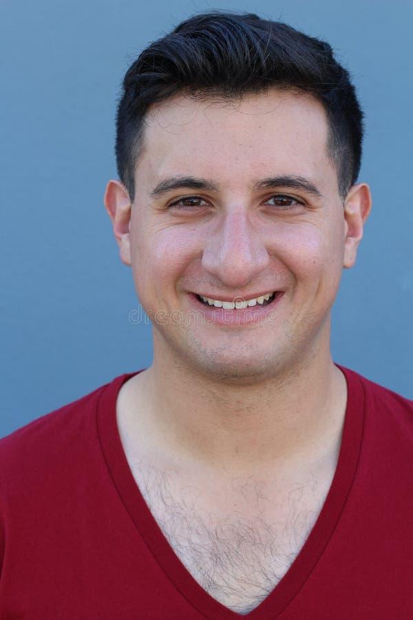 Портрет красивого молодого человека усмехаясь на камере, на сини стоковые фотографии rf