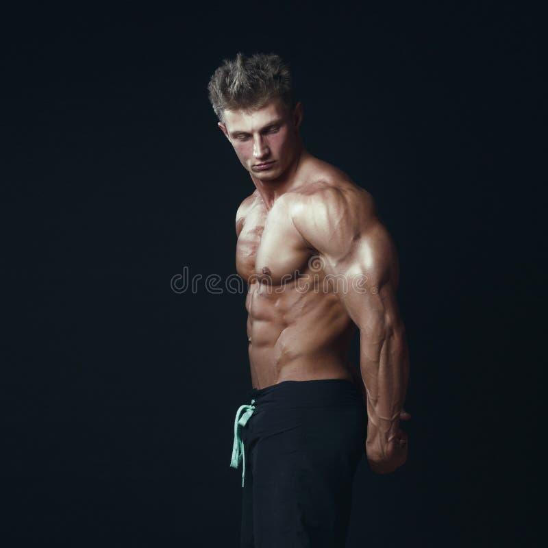 Портрет красивого мышечного культуриста представляя над черным ба стоковая фотография rf