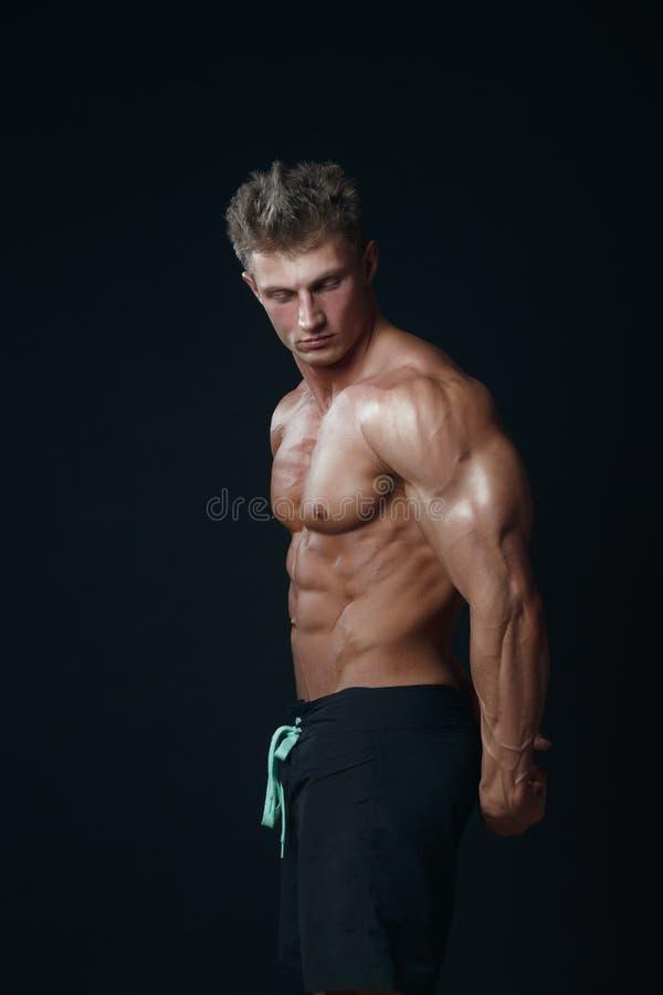 Портрет красивого мышечного культуриста представляя над черным ба стоковые фотографии rf
