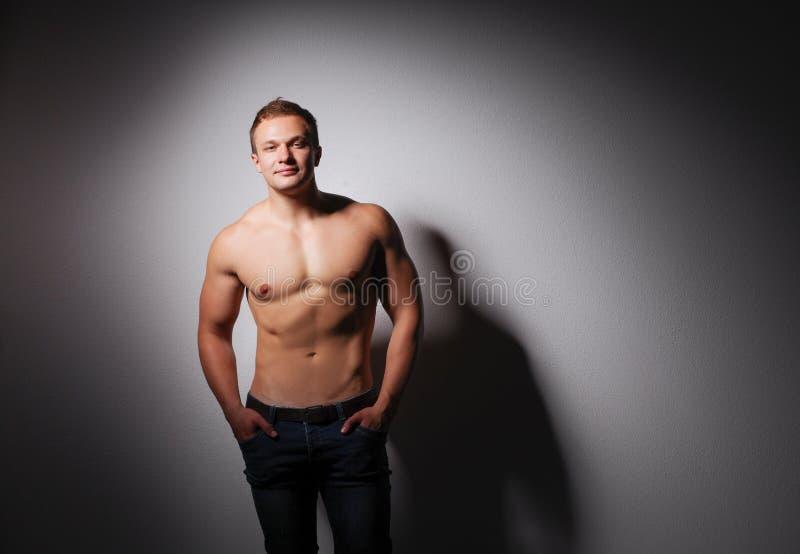 Портрет красивого мышечного положения человека над серой предпосылкой стоковые фотографии rf