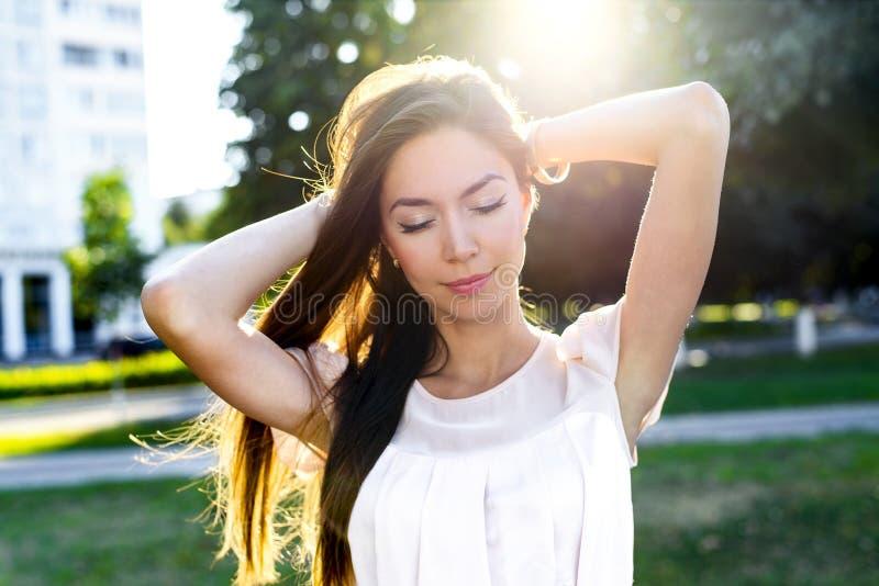 Портрет красивого парка брюнет держа волосы наслаждается вашими каникулами, в ярком солнечном свете стоковые изображения
