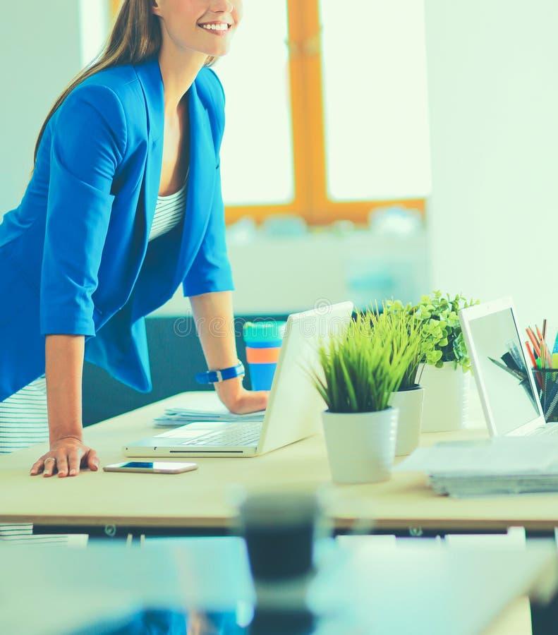 Портрет красивого положения бизнес-леди около ее рабочего места стоковая фотография rf