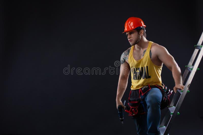 Портрет красивого построителя с лестницей конструкции на черной предпосылке стоковое фото rf