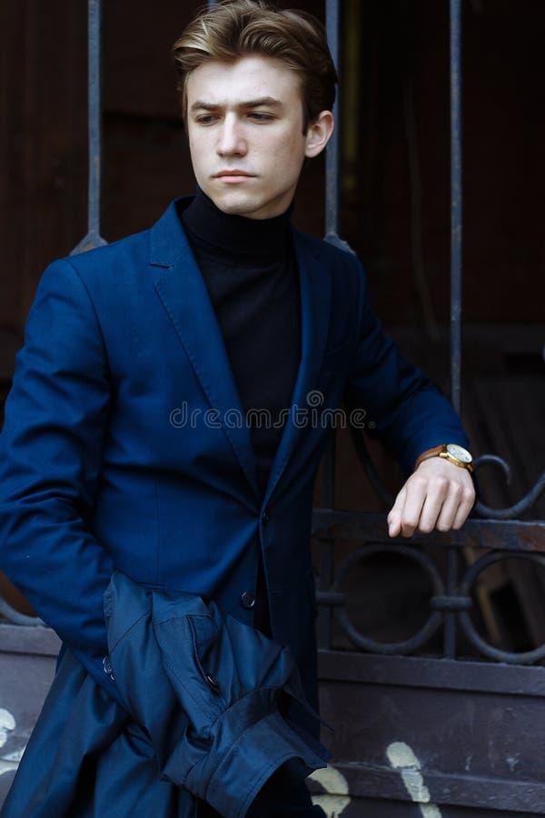 Портрет красивого, привлекательного, молодого человека в голубом костюме, пальто, в городе задумчивый и грустный, ждущ стоковое фото