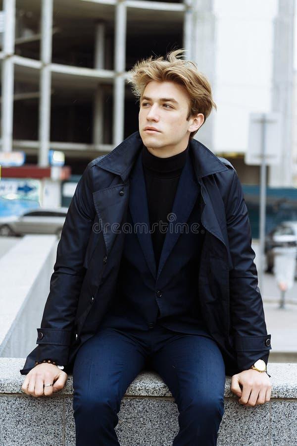Портрет красивого, привлекательного, молодого человека в голубом костюме, пальто, в городе задумчивый и грустный, ждущ стоковое изображение