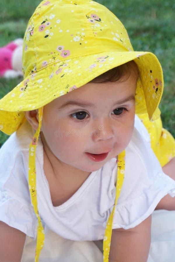 Портрет красивого ребёнка с глазами коричневого цвета и желтой шляпой стоковая фотография