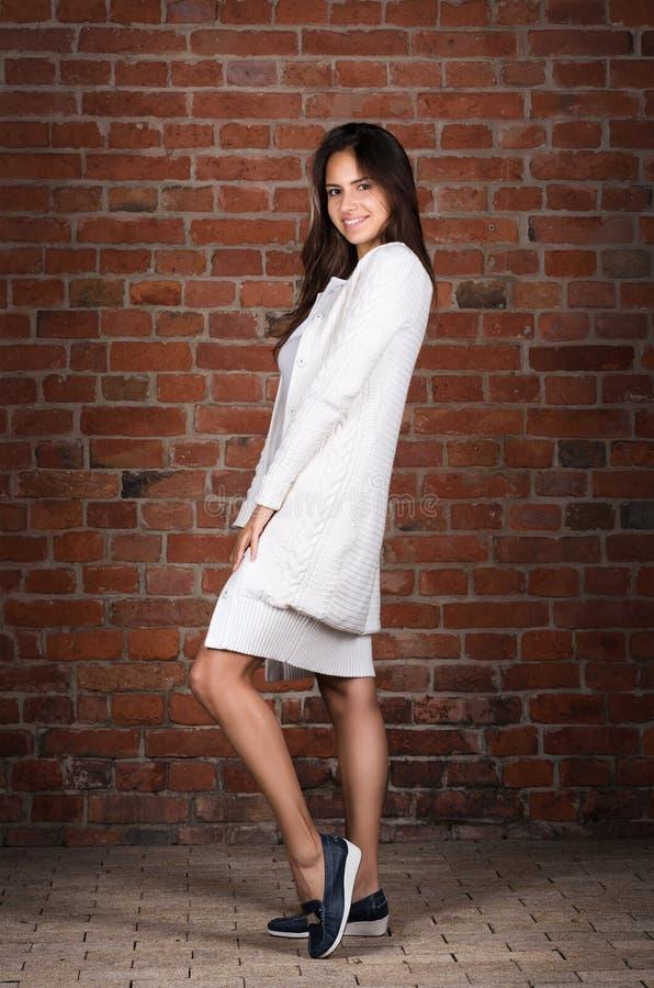 Портрет красивого роста молодой женщины полностью Вскользь носка, длинный белый свитер стоковые изображения rf