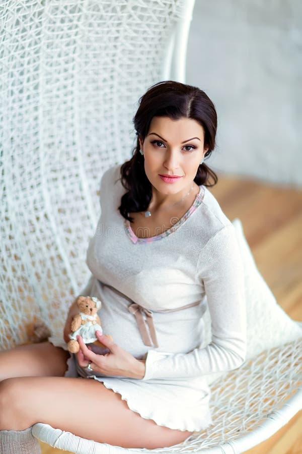 Портрет красивого сексуального беременного брюнет в белой студии w стоковые фото