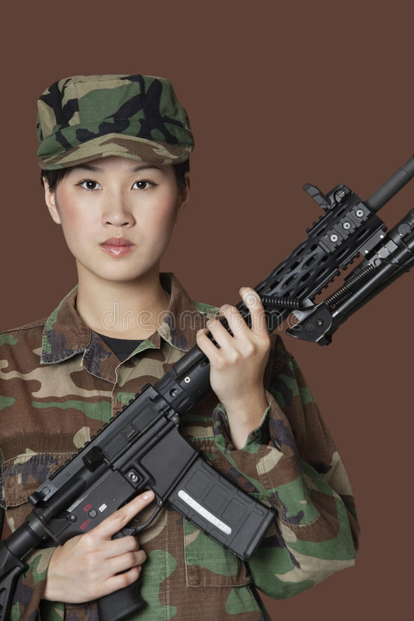 Портрет красивого солдата морской пехот США детенышей с штурмовой винтовкой M4 над коричневой предпосылкой стоковые фото