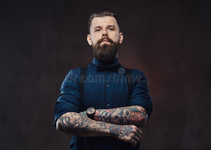 Портрет красивого старомодного битника в голубой рубашке и подтяжках, стоя с пересеченными оружиями в студии стоковые фото
