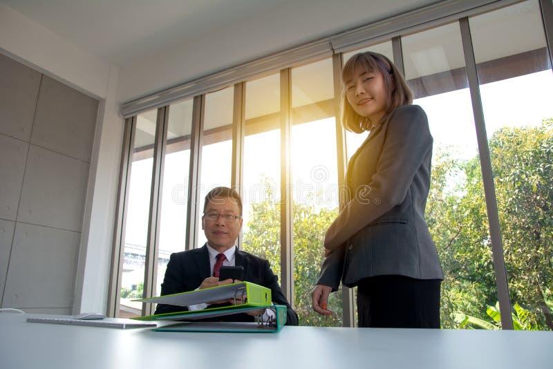 Портрет красивого уверенного бизнесмена в элегантном костюме смотря через отчет и его секретарше стоя на встреча стоковое фото