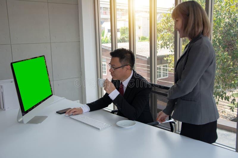 Портрет красивого уверенного бизнесмена в элегантном костюме смотря через отчет и его секретарше стоя рядом с ним стоковые изображения rf