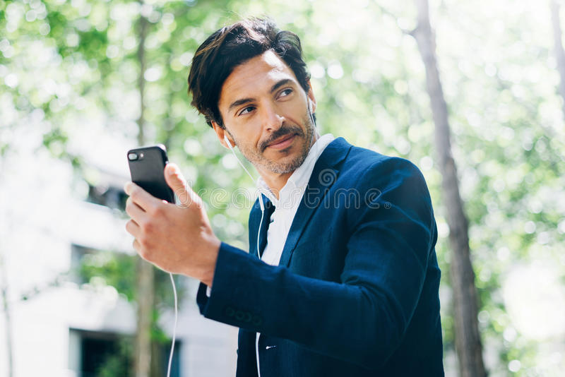 Портрет красивого усмехаясь бизнесмена используя smartphone для listining музыки пока идущ в парк города горизонтально стоковые фото