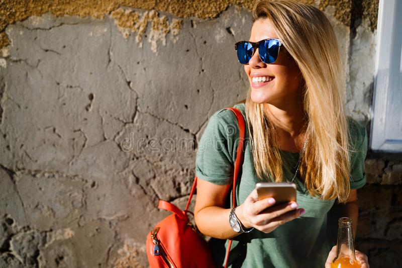 Портрет красивого усмехаясь сообщения сочинительства женщины в городе стоковые фотографии rf